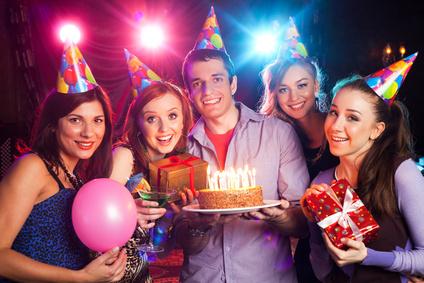 Geburtstagskind hält Torte vor Gästen