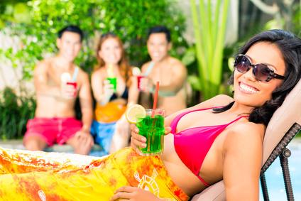Gäste feiern am Pool mit Cocktails