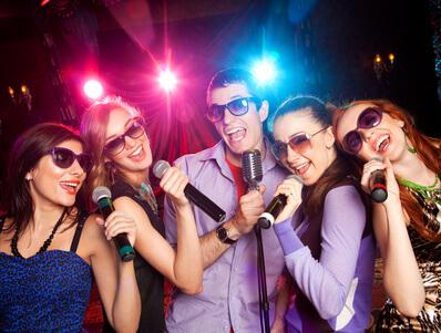 Feiernde Partygäste singen Karoke